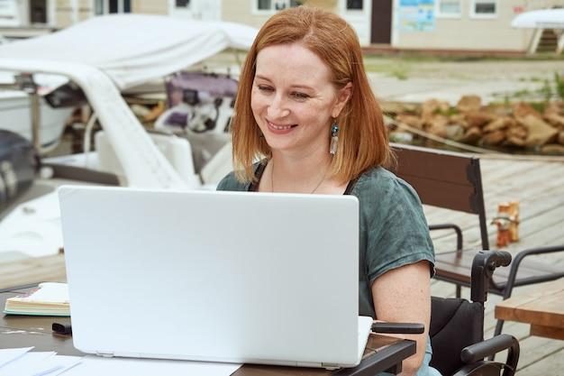 Glückliche behinderte frau verwendet laptop für fernarbeit in einem café im freien.