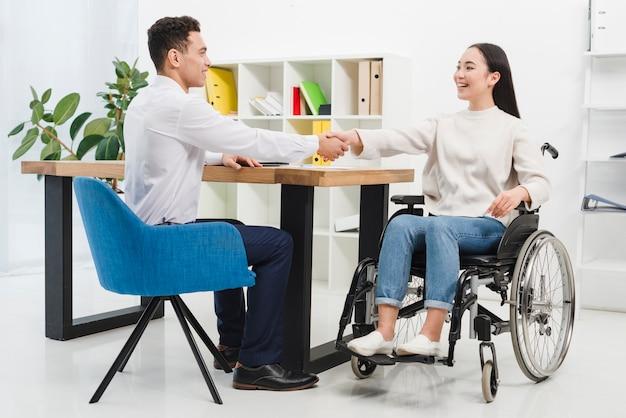 Glückliche behinderte junge frau, die auf dem rollstuhl rüttelt hände mit männlichem kollegen im büro sitzt