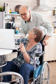 Glückliche behinderte seniorin im rollstuhl und ehemann, die während des videoanrufs auf dem laptop in der küche hallo sagen und lachen. gelähmte person, die moderne online-internet-web-kommunikation verwendet