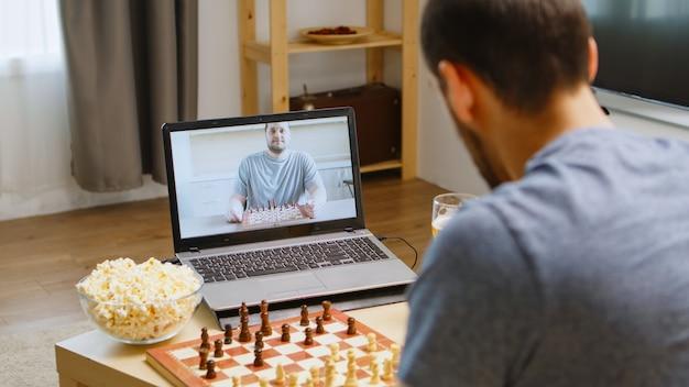 Glückliche beste freunde, die während der coronavirus-quarantäne schach per videoanruf spielen. bier trinken und popcorn essen.