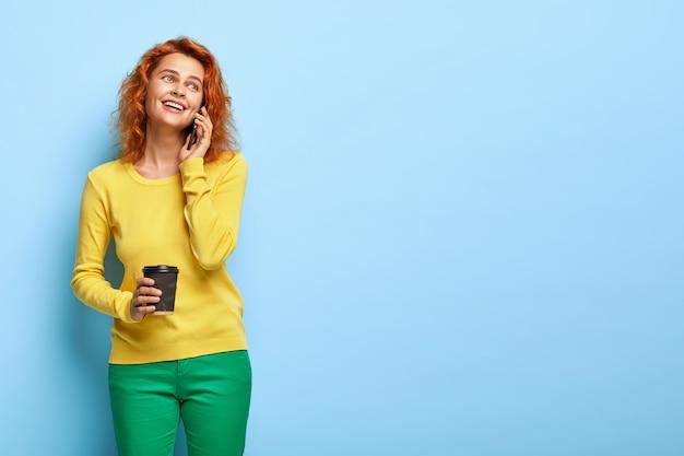 Glückliche blauäugige fuchsfrau ruft freund auf handy an, drückt positive emotionen aus