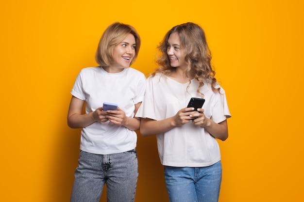 Glückliche blonde damen, die auf ihrem telefon plaudern