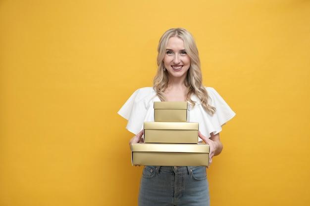 Glückliche blonde europäische frau in der weißen bluse, die eine packung geschenkbox hält
