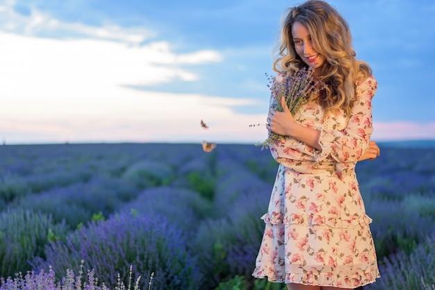 Glückliche blonde frau auf dem lavendelgebiet