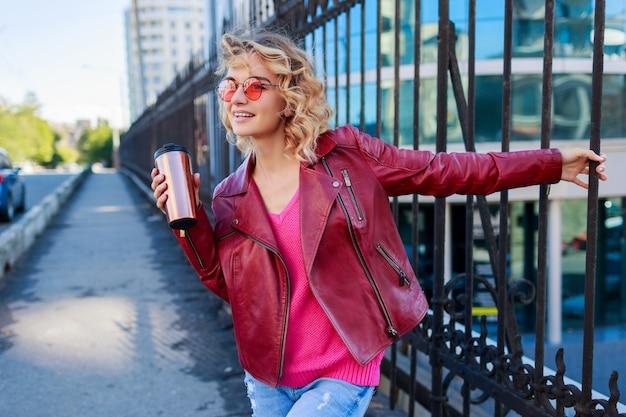 Glückliche blonde frau, die auf modernen straßen aufwirft, kaffee oder cappuccino trinkend. stilvolles herbstoutfit, lederjacke und strickpullover. rosa sonnenbrille.