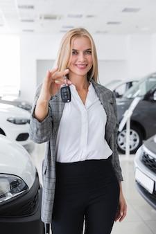Glückliche blonde frau, die autoschlüssel hält
