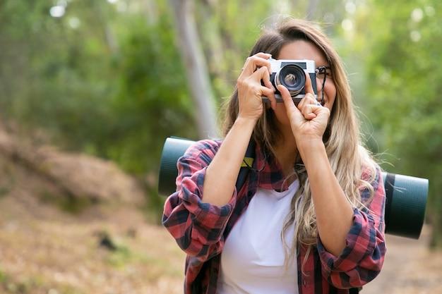 Glückliche blonde frau, die foto der natur mit kamera und lächeln nimmt. kaukasischer langhaariger reisender, der im wald geht oder wandert. tourismus-, abenteuer- und sommerferienkonzept