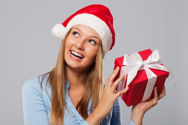 Glückliche blonde frau, die kleines rotes geschenk hält