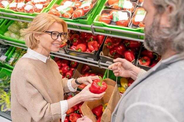 Glückliche blonde frau, die roten reifen paprika auf anzeige mit frischem gemüse wählt und es in papiertüte legt, die von ihrem ehemann gehalten wird