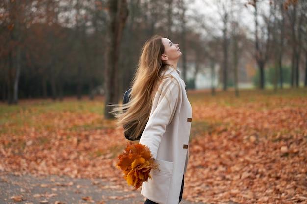 Glückliche blonde frau, die trendigen herbstmantel und schwarze jeans trägt