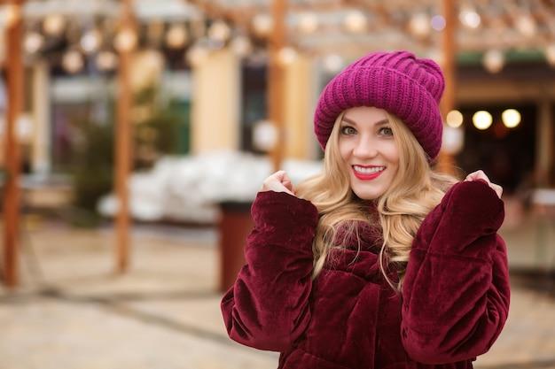 Glückliche blonde frau, die warme winterkleidung trägt und auf dem hintergrund der lichter posiert