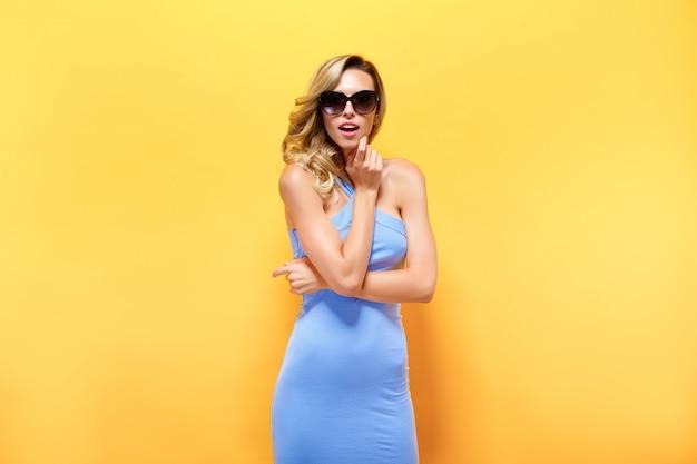 Glückliche blonde frau im blauen kleid auf gelber wand