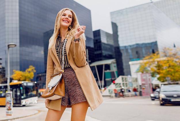 Glückliche blonde frau im frühjahr lässiges outfit, das draußen geht und ferien in der großen modernen stadt genießt. trägt einen beige wollmantel und eine abgestreifte bluse. stilvolles zubehör.
