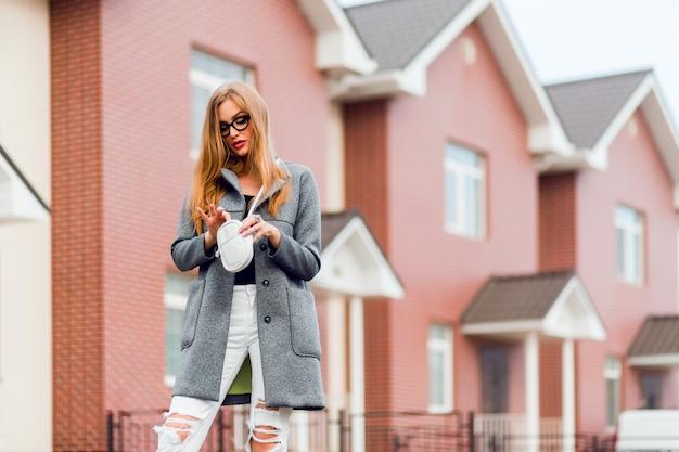 Glückliche blonde frau im grauen mantel posng im freien. herbststimmung.