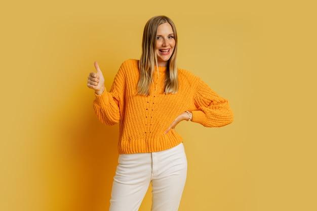 Glückliche blonde frau im orange stilvollen herbstpullover, der auf gelb aufwirft. zeichen ok zeigen.