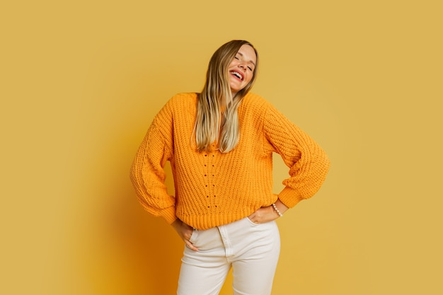 Glückliche blonde frau im orange stilvollen herbstpullover, der auf gelb aufwirft.