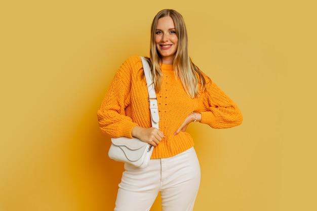 Glückliche blonde frau im trendigen herbstoutfit posiert auf gelb. halten weiße ledertasche.