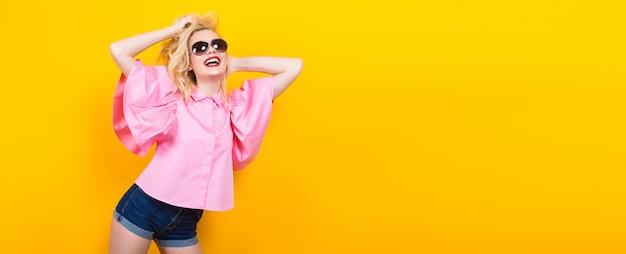 Glückliche blonde frau in der rosafarbenen bluse mit sonnenbrillen