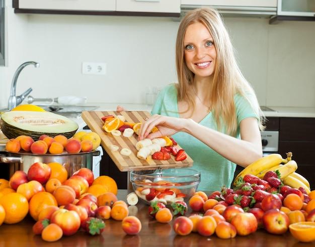 Glückliche blonde frau kocht mit reifen früchten