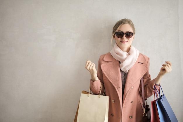 Glückliche blonde frau mit einkaufstüten