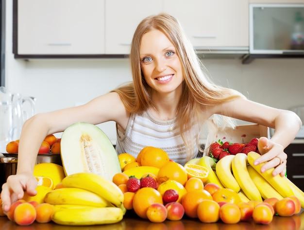 Glückliche blonde frau mit haufen von früchten