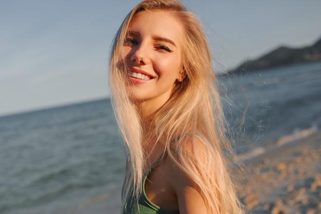 Glückliche blonde frau mit perfektem lächeln, das spaß am sonnigen strand hat, kamera betrachtet, läuft und tanzt