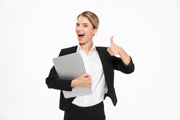 Glückliche blonde geschäftsfrau, die laptop-computer hält und daumen oben zeigt, während über weißer wand
