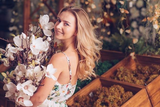 Glückliche blonde junge frau, die in der hand kamelienblumenstrauß hält