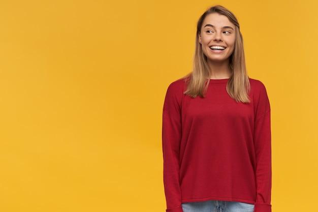 Glückliche blonde junge frau, die vom glück scheint, mit neugierigem interesse nach links schauend, auf der rechten seite stehend, freier raum für text