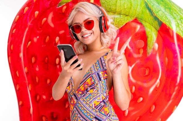 Glückliche blonde kaukasische frau steht im badeanzug mit der großen gummimatratze, telefon, kopfhörern, tun selfie und das lokalisierte lächeln