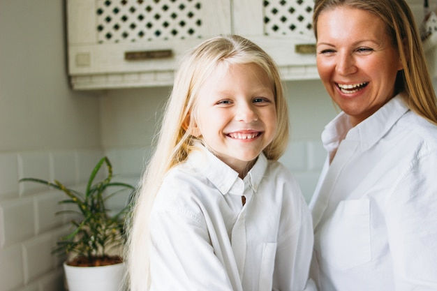 Glückliche blonde lange haarmutter und -tochter, die spaß in der küche, gesunder familienlebensstil hat