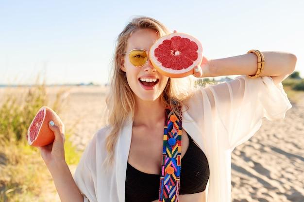 Glückliche blonde natürliche frau, die grapefruit hält. gesunde diätnahrung. sommerurlaub .