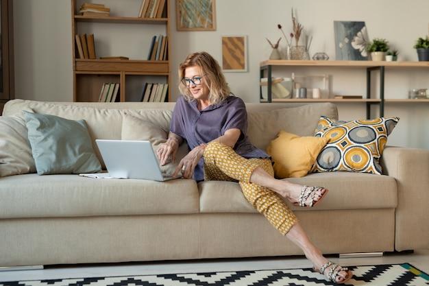 Glückliche blonde reife frau, die auf bequemer couch im wohnzimmer vor laptop sitzt, während durch video-chat kommuniziert