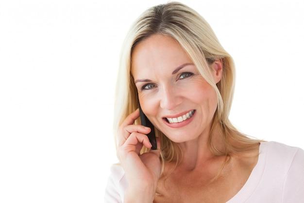 Glückliche blondine, die am telefon spricht