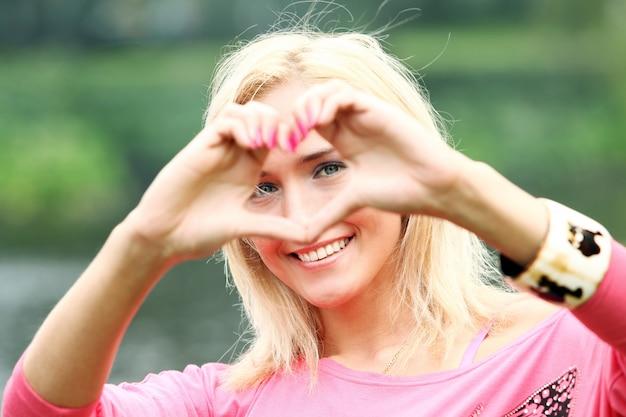 Glückliche blondine, die herz mit ihren händen bildet