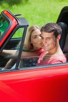 Glückliche blondine, die ihren freund im roten cabriolet küsst