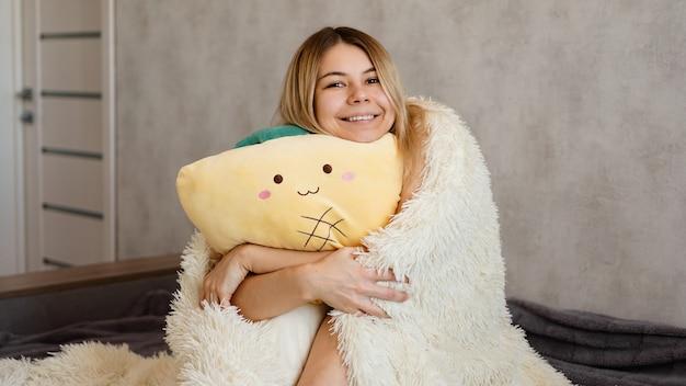 Glückliche blondine unter einer weißen decke am morgen umarmt ein gelbes kissen. happy morning konzept