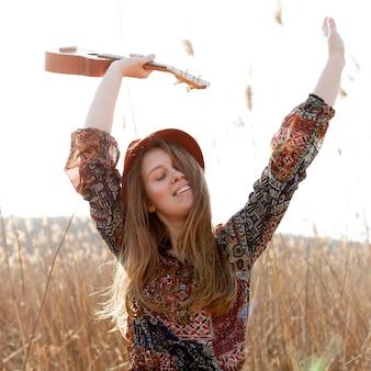 Glückliche böhmische frau, die beim halten der ukulele aufwirft