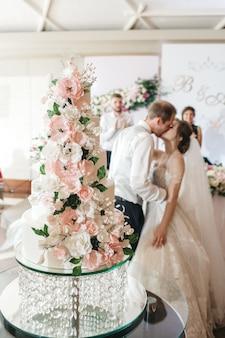 Glückliche bräute küssen einen kuchen an ihrem hochzeitstag