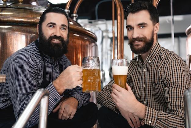 Glückliche brauer trinken helles bier aus glas und becher.
