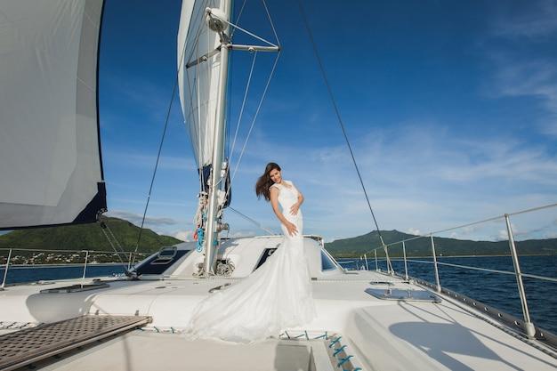 Glückliche braut auf einer yacht. weiße yacht mit segelsatz fährt entlang der insel