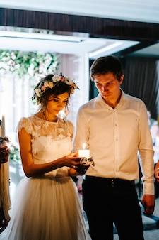 Glückliche braut, die eine kerze und einen bräutigam neben ihr hält