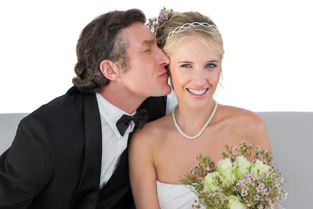 Glückliche braut, die vom bräutigam geküsst wird