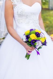 Glückliche braut hält einen hochzeitsblumenstrauß in den händen. hochzeitsstrauß aus lila, gelben und weißen blumen in ihren händen und eine junge braut.