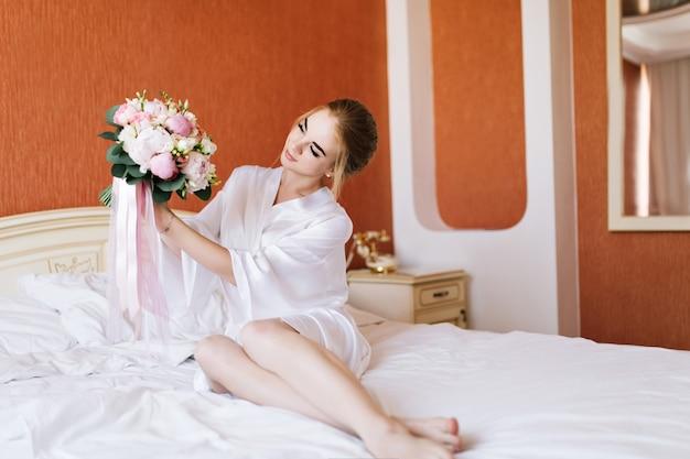 Glückliche braut im weißen bademantel mit blumen auf bett am morgen. sie sieht glücklich aus