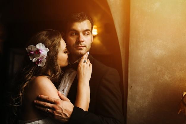 Glückliche braut mit dem gesicht auf bräutigam hals