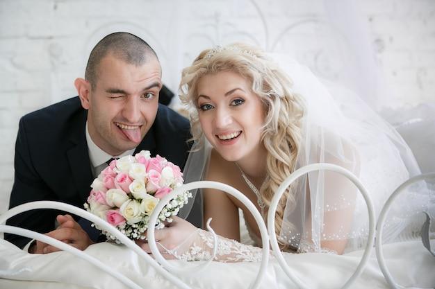 Glückliche braut mit einem hochzeitsstrauß aus rosen und der fröhliche bräutigam, der die zunge herausstreckt, liegen auf einem bett im schlafzimmer