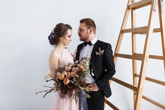Glückliche braut und bräutigam auf leiter am studio. weißer wandhintergrund lokalisiert
