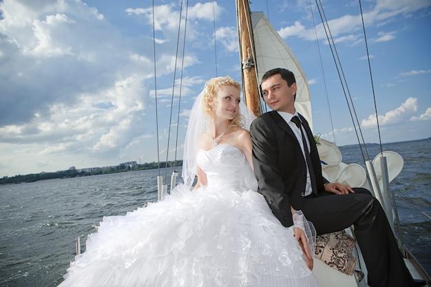 Glückliche braut und bräutigam, die auf einer yacht umarmt