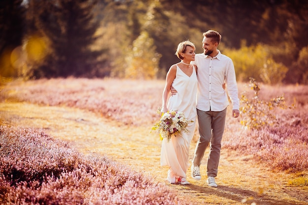 Glückliche braut und bräutigam gehen über das violette feld